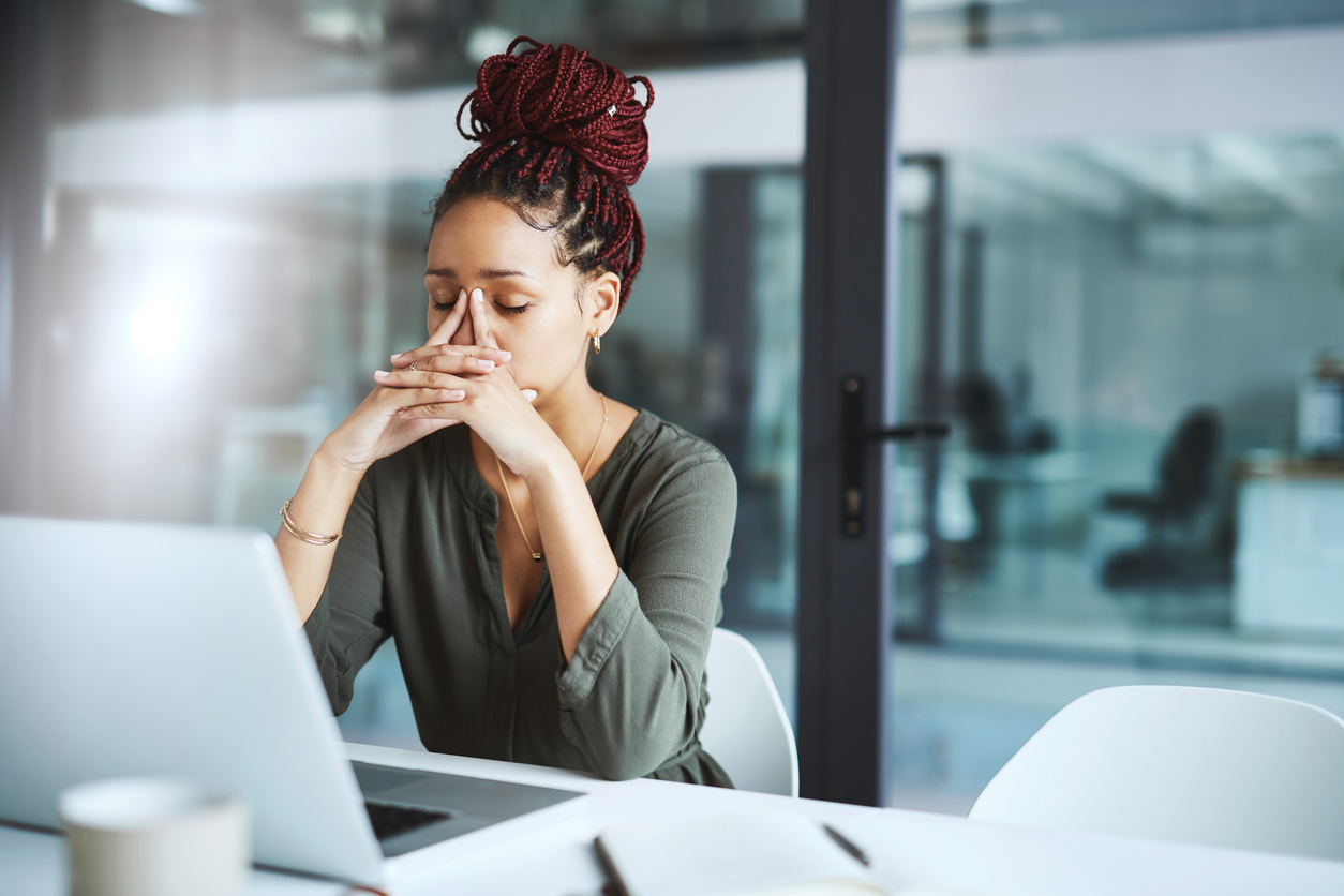 Young black small business woman looking stressed at her computer while working on her website design.