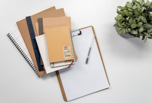 Clipboard with paper and a stack of brown notebooks.