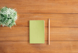 A green notebook and wooden pencil on a wooden slated desk
