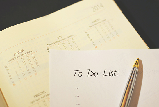 Paper to do list on top of a paper calendar.