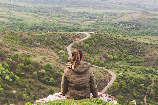 A woman with brown hair overlooking a valley with a road going through it